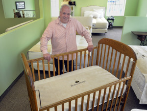Rory Karpathian, President of Beds by Design, with a mattress made for infants, pictured at his Rochester location, Thursday April 23, 2015. (Photo by: Vaughn Gurganian)